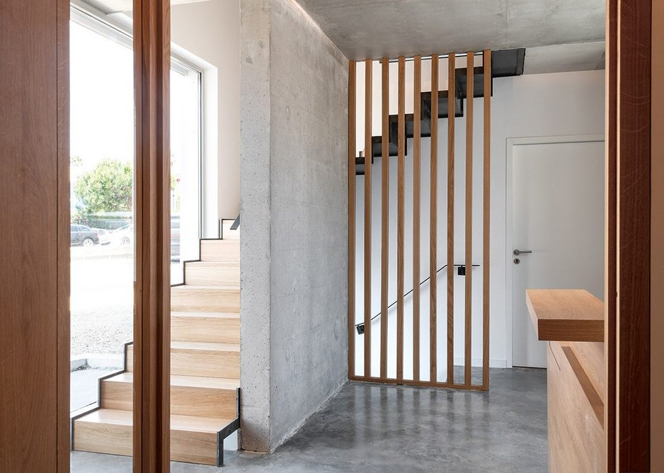 The exposed concrete and timber reception area on the ground floor.