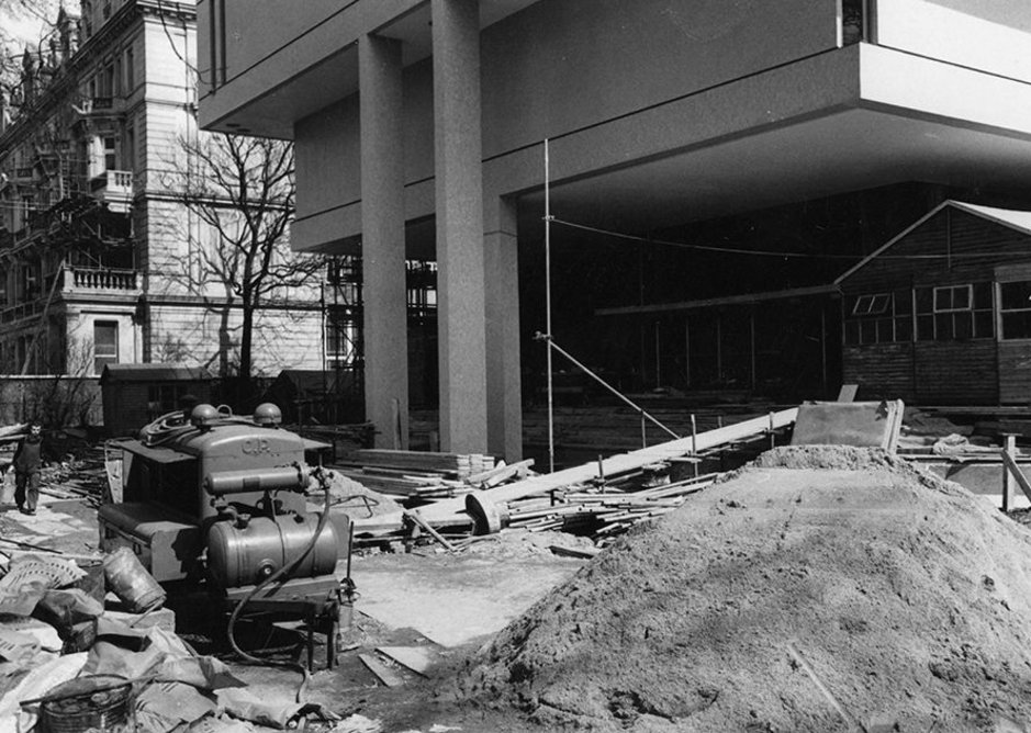 RCP construction works   Lasdun's ambitious design for the RCP presented major engineering challenges. He wanted to extend the Dorchester Library outwards, so that it appears to 'float' unsupported above the main entrance.   This was achieved through cantilevers (horizontal beams extended into the main building to balance the weight of the library), 49 ft concrete beams, reinforced steel rods, and the three thin pillars at the entrance.   The RCP building is predominantly made of concrete, poured on site into wooden moulds. A lot of steel was used within the concrete, often tightened once the concrete had set but before the moulds were removed, to maximise its strength and help support Lasdun's large rooms. The rough concrete was then clad in either mosaic tiles and engineering bricks, or left exposed.
