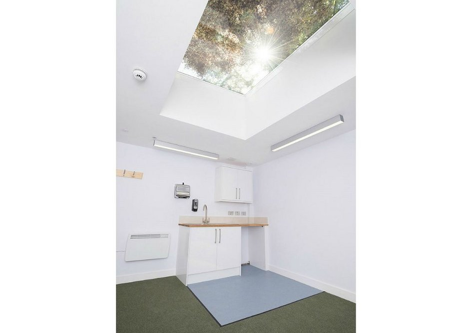 A large fixed rooflight allows light to enter the part-subterranean building despite it being surrounded by walls.