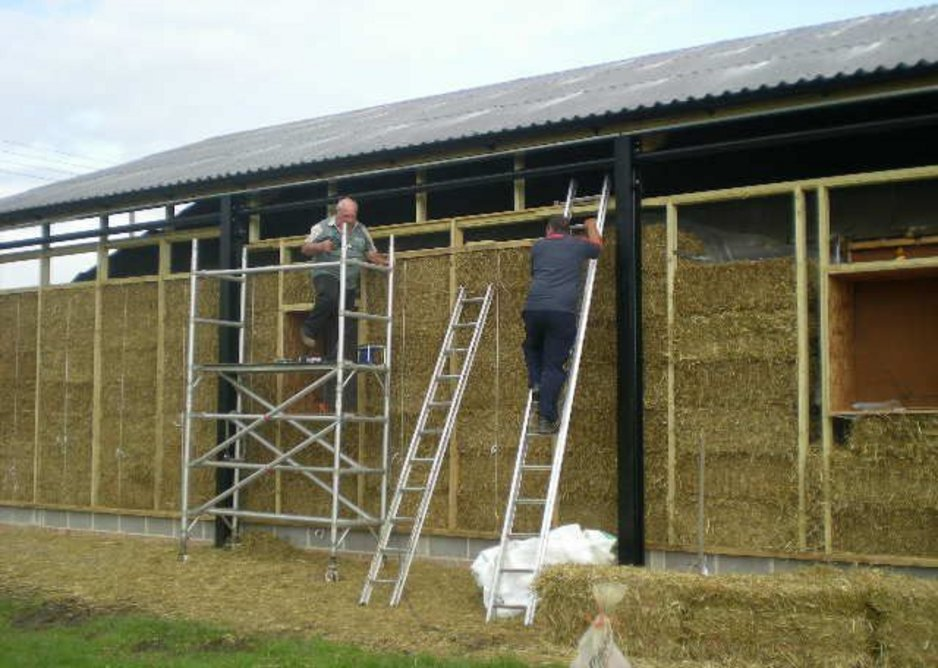 The straw bale walls going up under the steel frame agricultural structure.