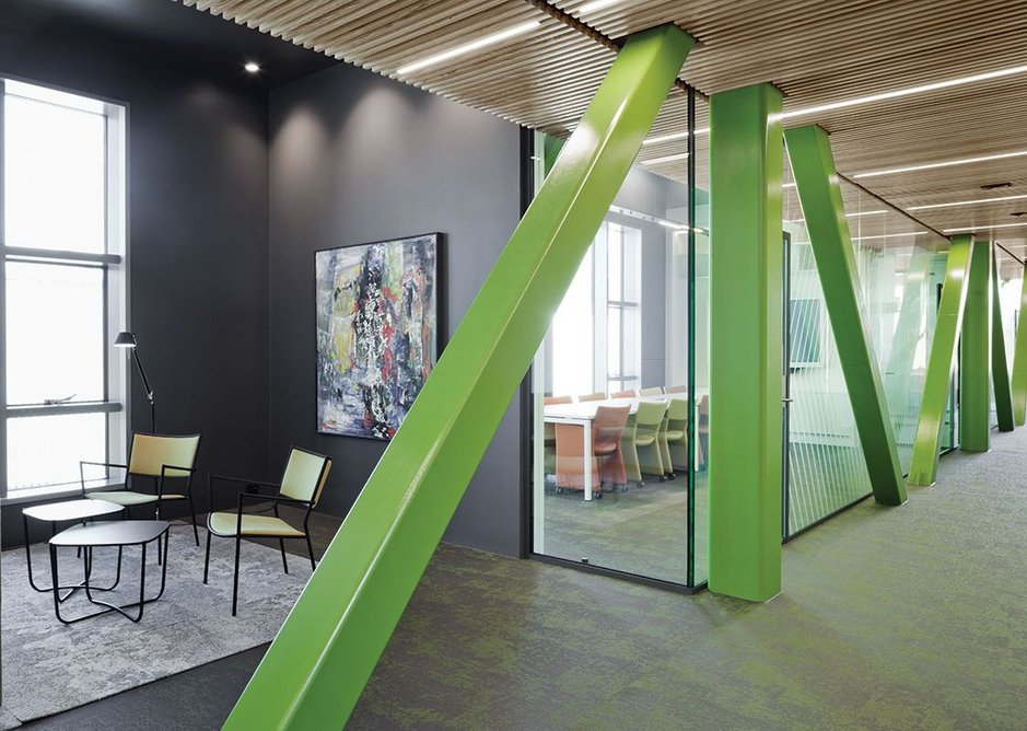 The truss structure of the raised office accommodation deck is expressed in bright green.