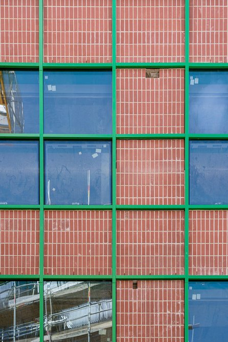 Detail of one of the two buildings at the Design District designed by David Kohn Architects. Both share green grids and heavy red masonry bases.