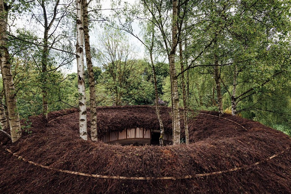 Silence - Alone in a World of Wounds, 2021, by Heather Peak and Ivan Morison (Studio Morison).Trees protruding through the pavilion, which is designed to gradually disintegrate over time. Photo © Charles Emerson, Courtesy The Oak Project and Yorkshire Sculpture Park