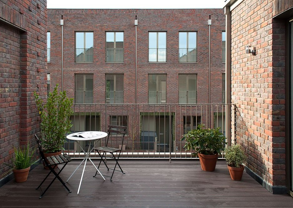 First floor terraces create contemporary relationships with the opposite side of the street while brick 'blind window' details suggest a previous history.