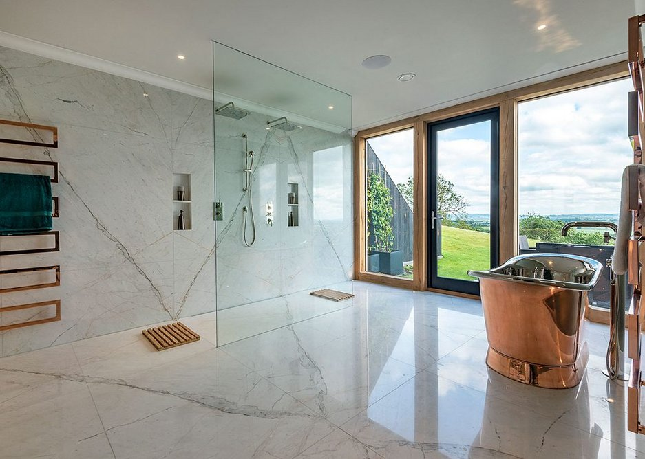 One of the bathrooms with book matched marble panels to walls and floor and a wet room shower.