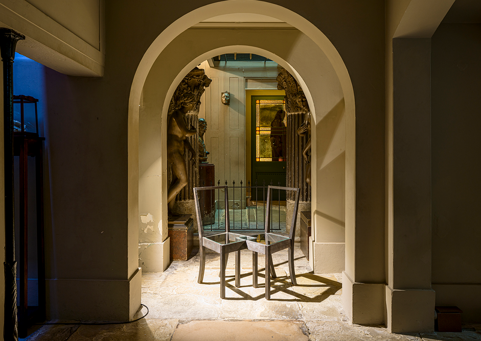 Installation view in the crypts of Langlands & Bell - Degrees of Truth at Sir John Soane's Museum showing Burnt Interlocking Chairs, 1997. Artists' collection.