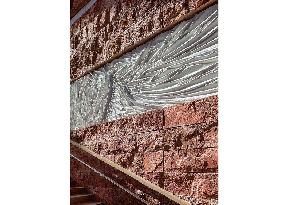Designer Iris van Herpen's frieze of fabric-like concrete intersperses the strata of cleft Iranian travertine.
