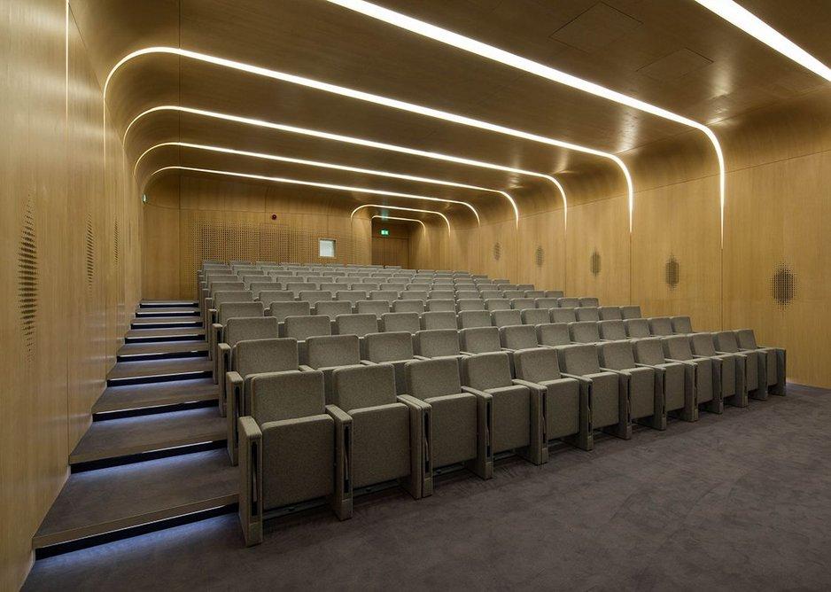 The oak-veneered auditorium, with loudspeakers behind wall perforations.