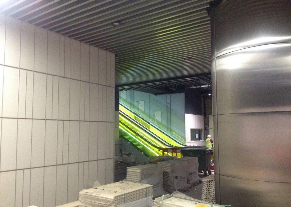 Yellow-sided escalators up from platform level.