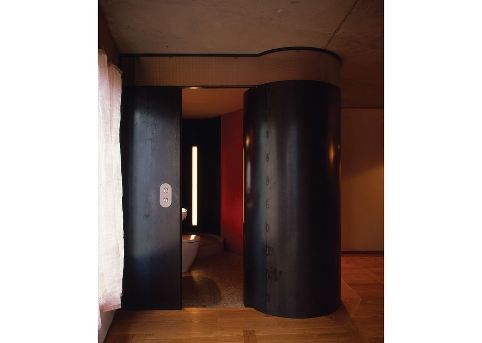 Bathrooms are discrete pod 'mechanisms' formed of a cavity wall of sheet steel, painted in 'reactive colours' that respond immediately to light and dark.