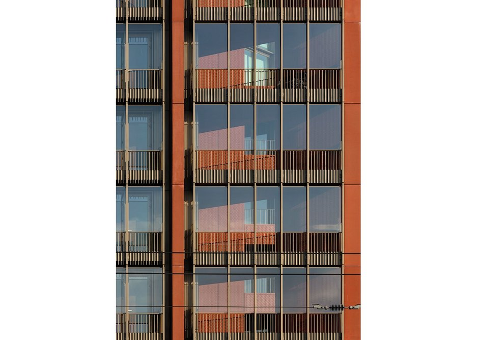 Detail of facade, with terracotta red cladding alongside Schueco glazing systems.