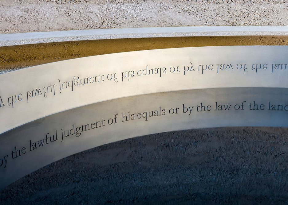 The words or Magna Carta clause 39 are legible in reflection in the water.