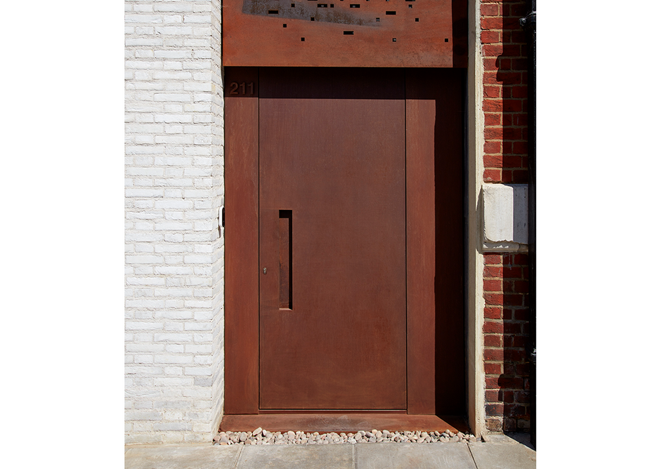 Urban Front Raw e90 steel doorset in Rust with concealed handle and matching panels to the side.