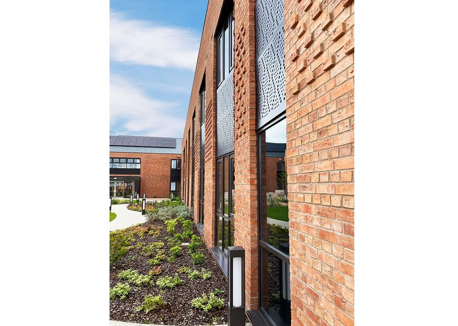 Care centre courtyard – perforated bronze panels take their patterns from original hosiery machine punch cards. Credit Glancy Nicholls Architects