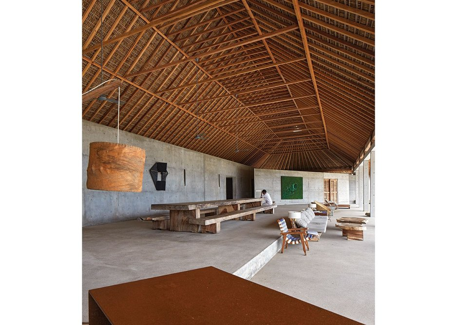 The pitched roof thatching over the communal room is left exposed, following the traditional format.