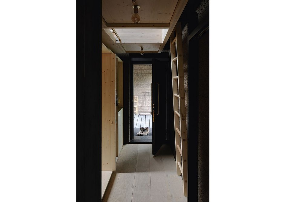 An apparently narrow entrance corridor works hard housing coats, ladder to reach the sleeping mezzanine and a pantry space for food preparation and washing up.