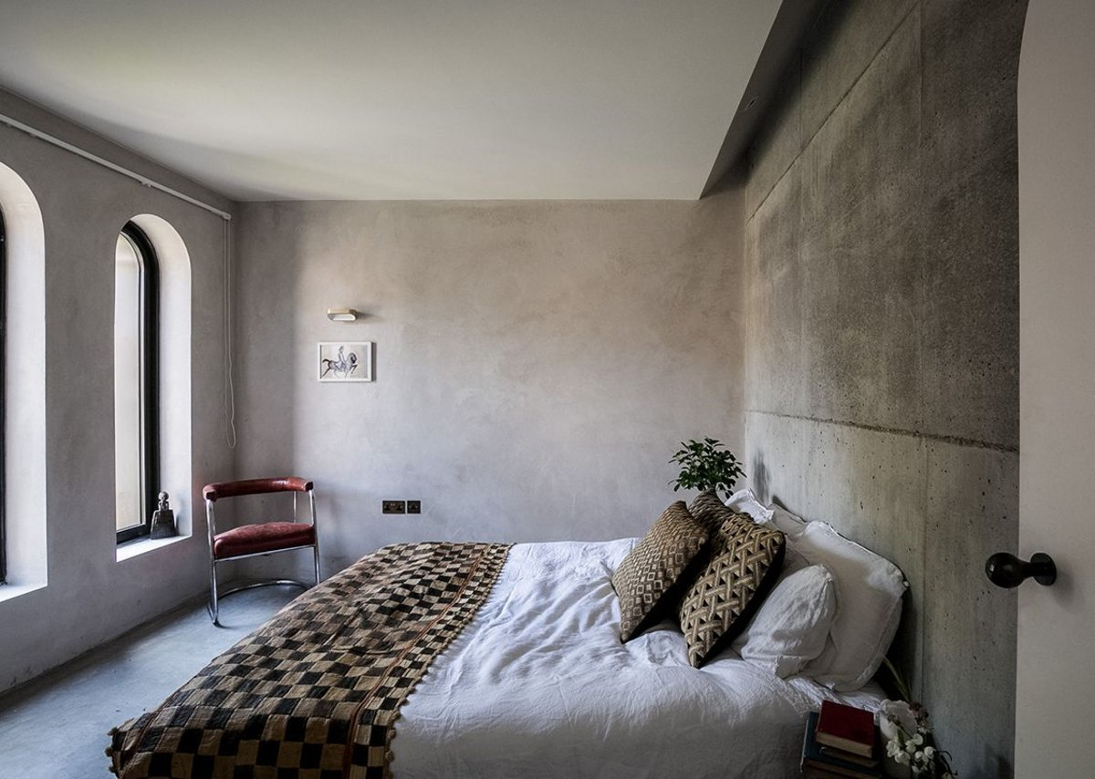 The main bedroom has a mix of raw concrete walls and clay plaster.