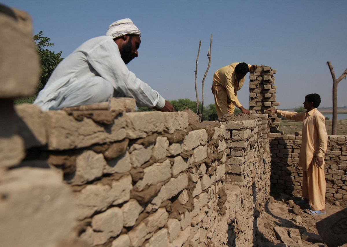 Villagers build a flood-proof mud brick house to Yasmin Lari's design.