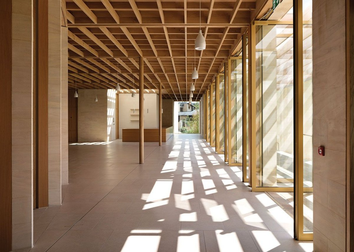 Slender timber columns reach up beyond the dappled light of the pergola. Grids and vanishing points all seem to take you somewhere beyond the cool interior.