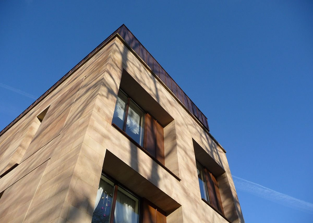 Deep-set window apertures with copper details including sills