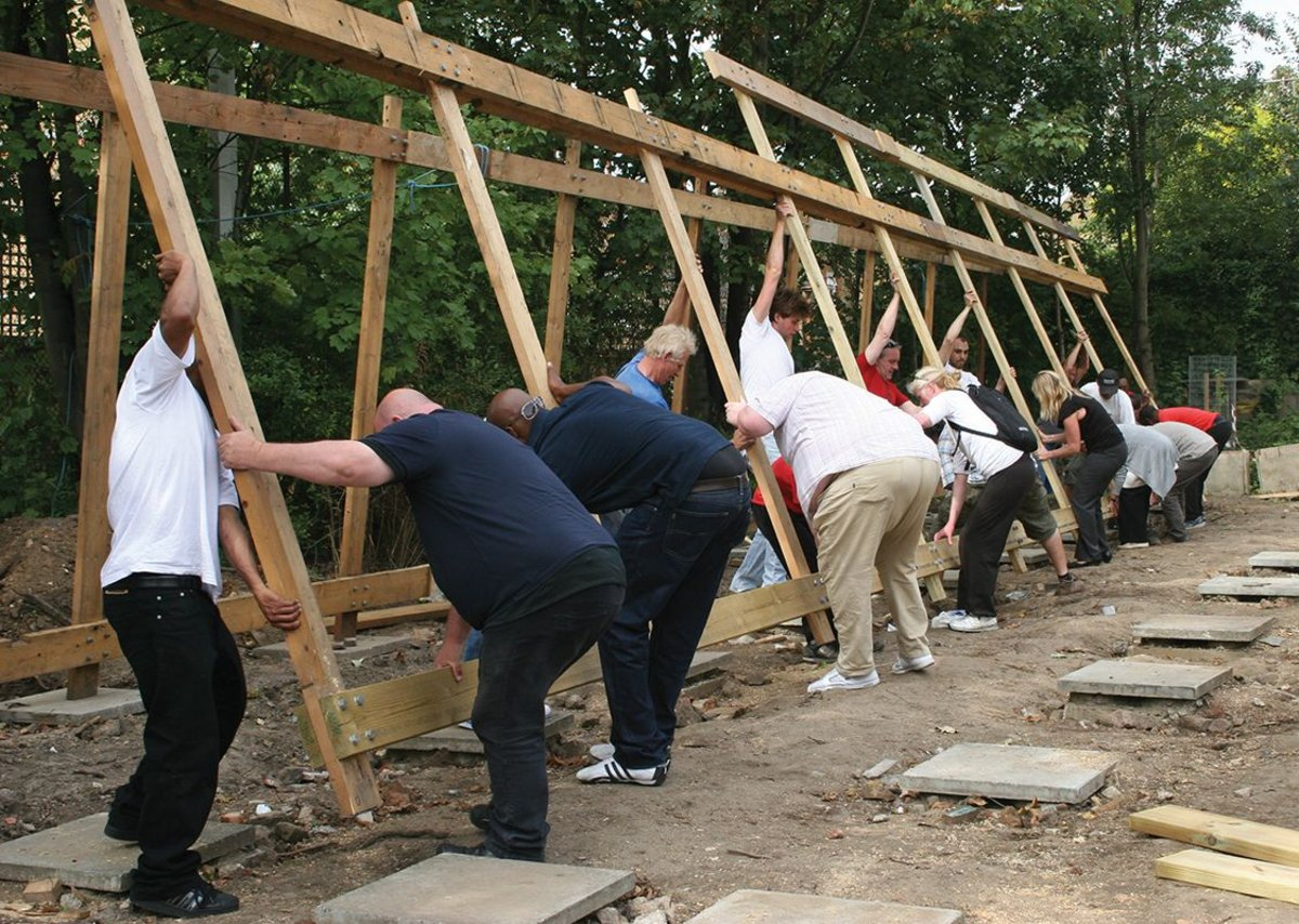 A squad of volunteers helps to reassemble the reborn building on its minimal foundation pads.