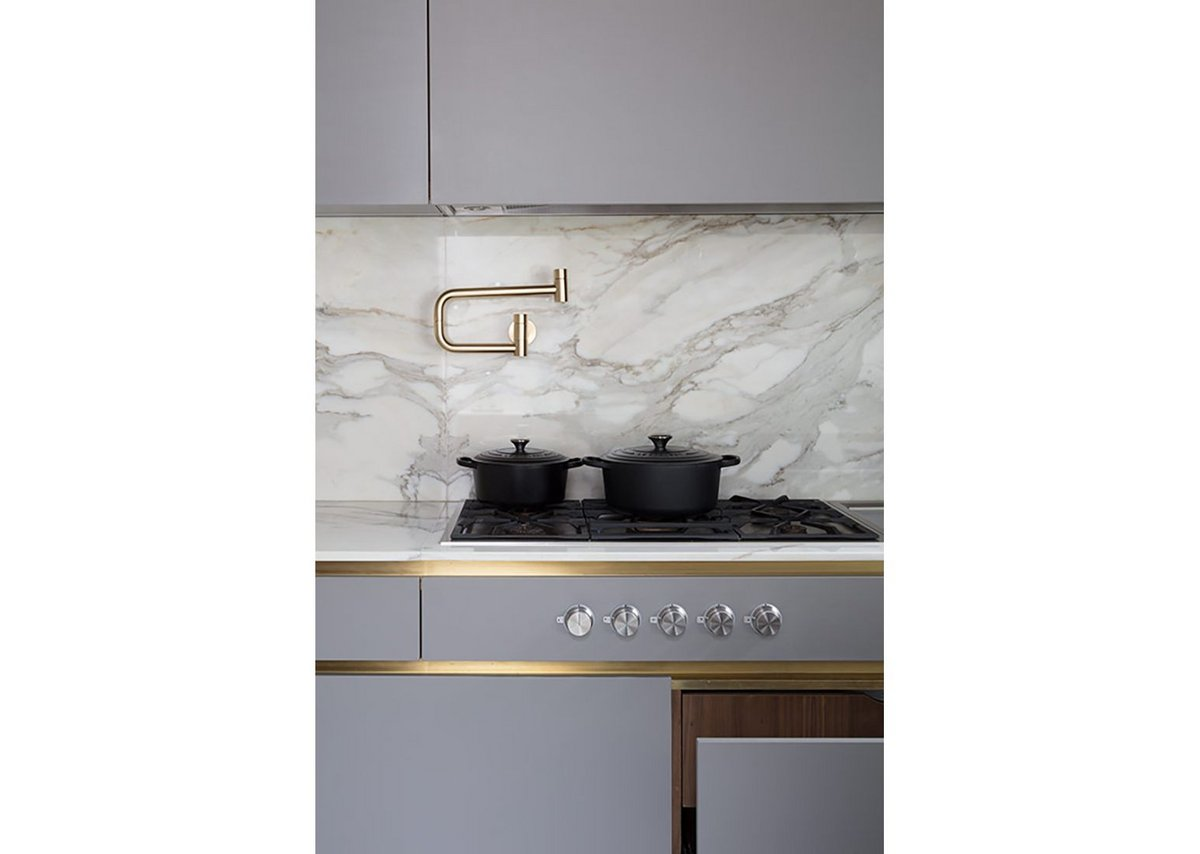 A matt lacquer bespoke kitchen and brass sheet cladding and detailing with Calacatta Oro marble work surfaces.