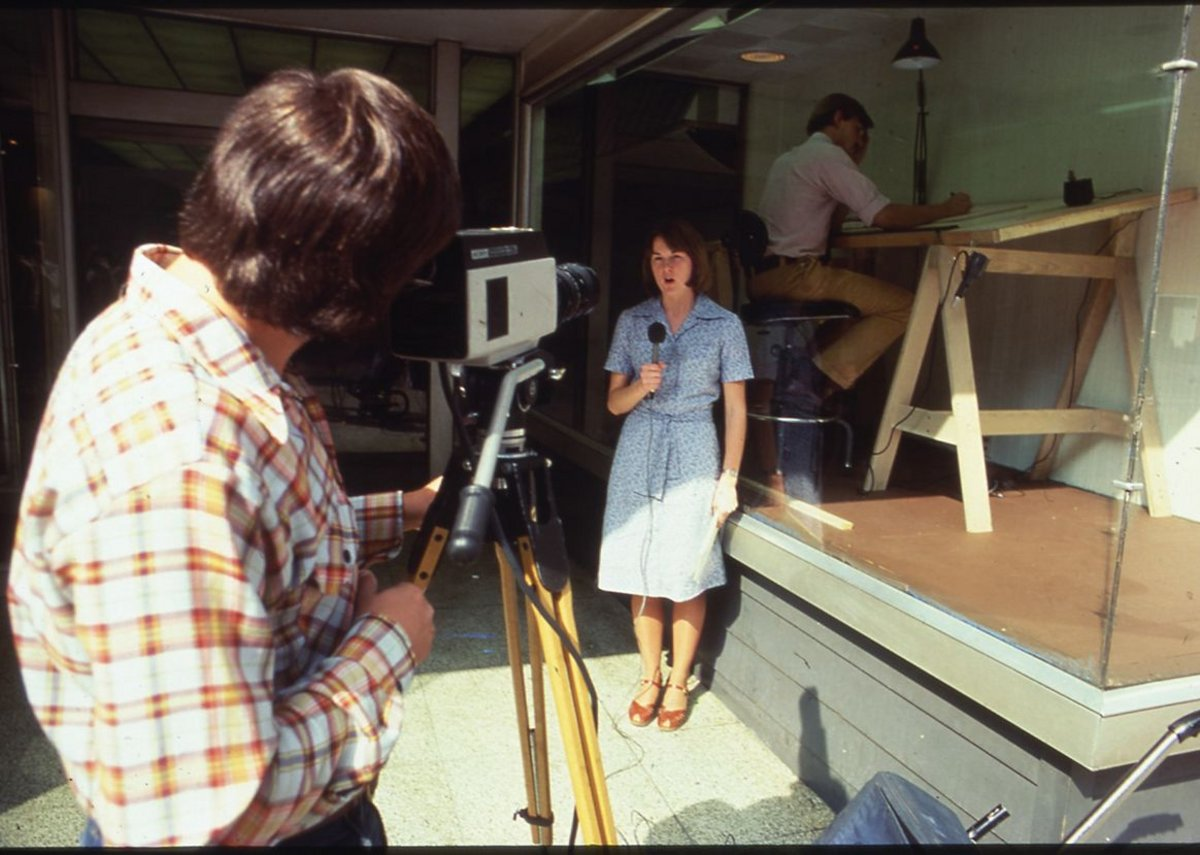 An architect from Moore Grover Harper at work while on display in the window of the Riverdesign Dayton storefront office, 1976.