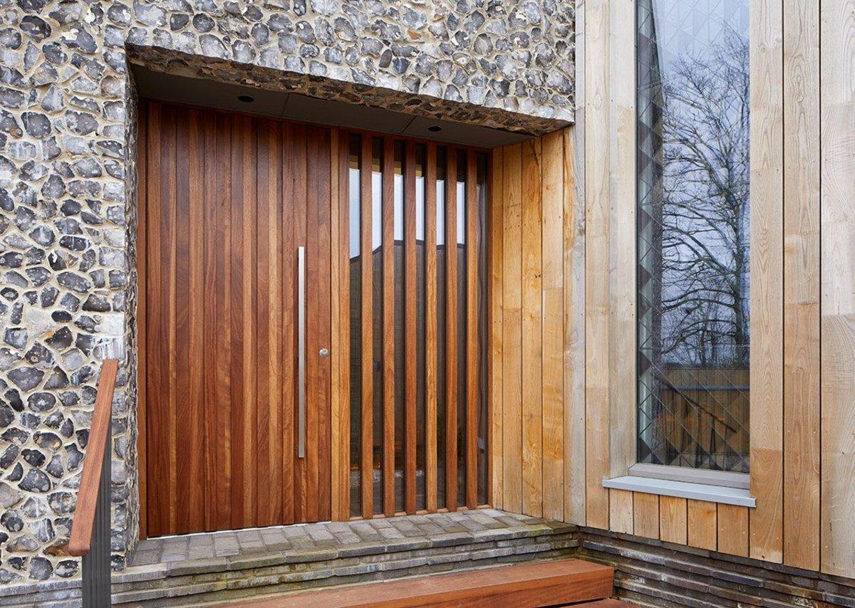 Bespoke pivot door in Iroko with Option 11 handle.