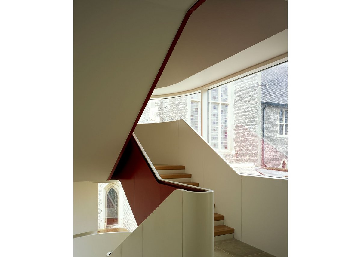 The winding steel stair overlooks the courtyard by the main entrance, its underside painted bright red.