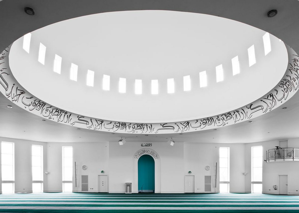 The interior of the Baitul Futuh Mosque is restrained and simple, with a large central dome and floor to ceiling windows.