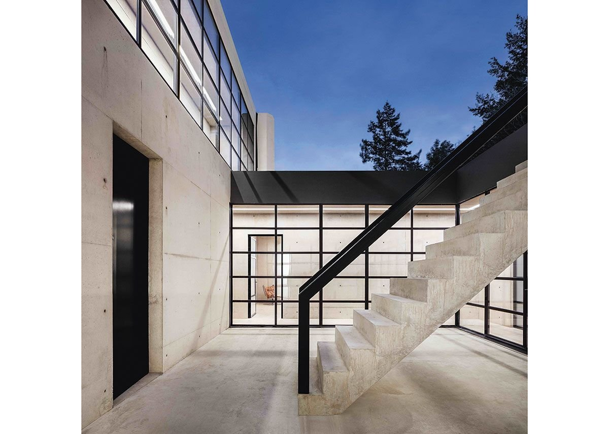 A stair from ground floor leads down to the entrance courtyard and front door, following the existing contours of the land.