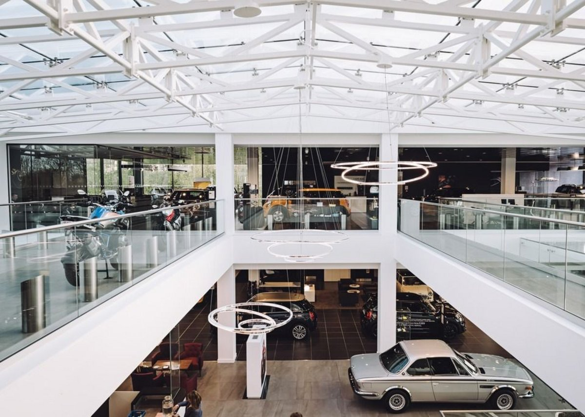 Ultra-transparent glass balustrades keep the Cotswold Cheltenham BMW showroom bright and the stock fully visible.