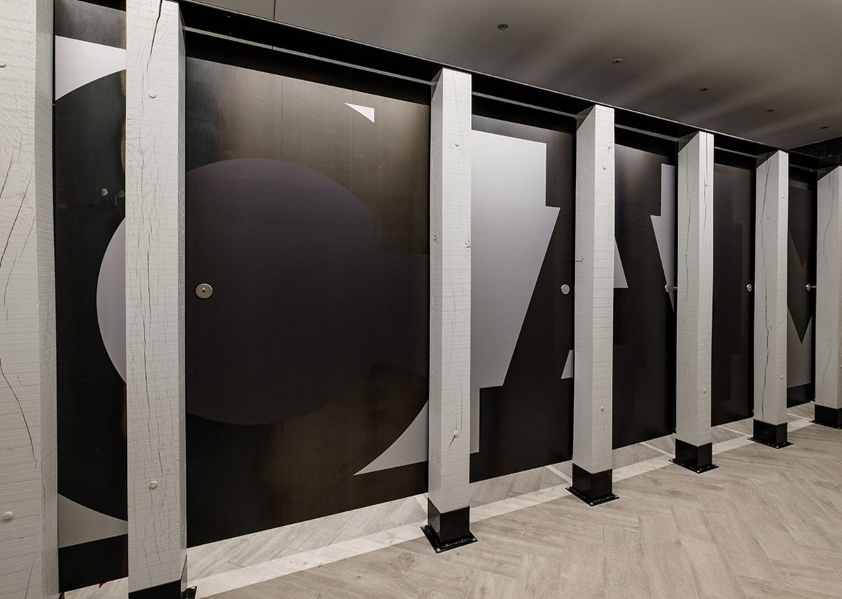 Bespoke vinyl graphic lettering spells out 'Camden' across the toilet cubicle doors in Stables Market.