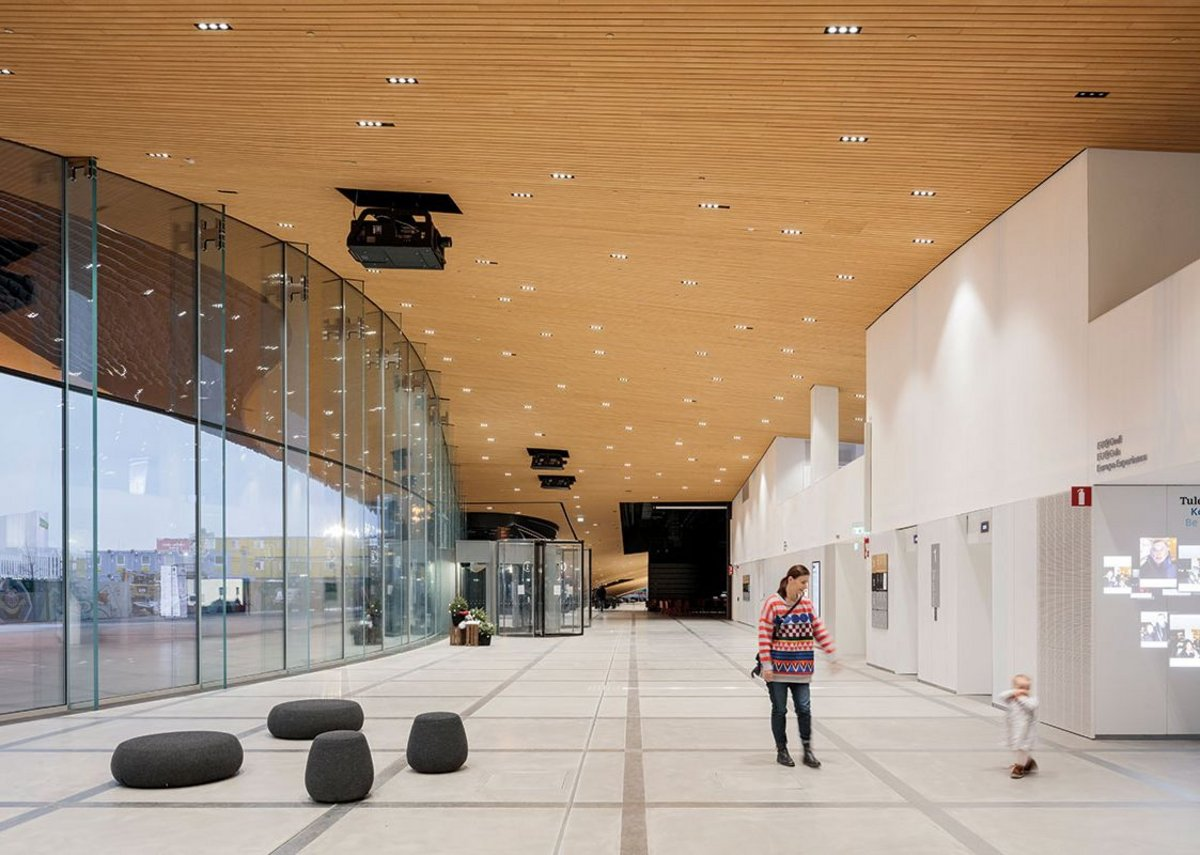 The ground floor looking north. The timber soffit of the cantilever draws the eye to the auditoria at the far end.