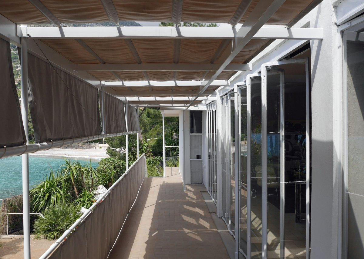 Folding glass wall opens onto shaded balcony.