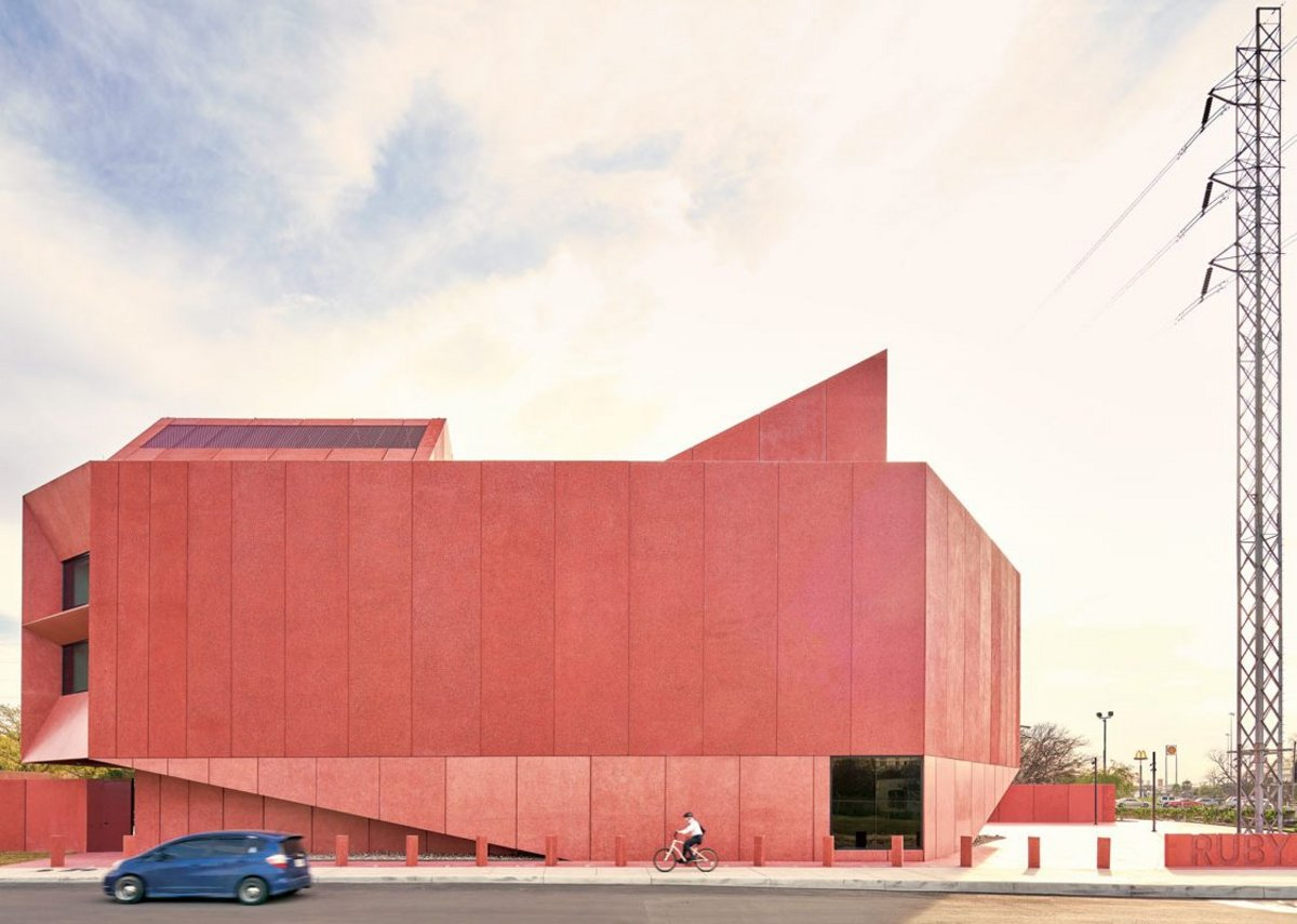 Red concrete panels that shimmer in the light clad this 1,300m2 gallery, Ruby City in San Antonio, Texas.