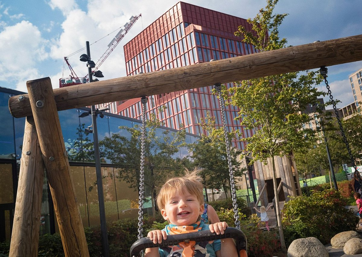 "Happy in the adventure playground, with the Duggan Morris ""Pink Building"" behind."