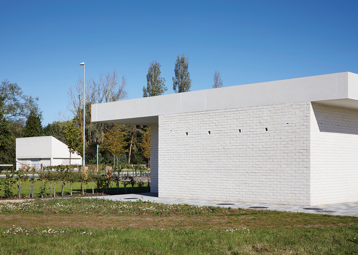 The short elevation of the sports pavilion with the electrical substation beyond. Homes for birds and bats have been created in the cavity walls, accessed via two types of hole in the facade.