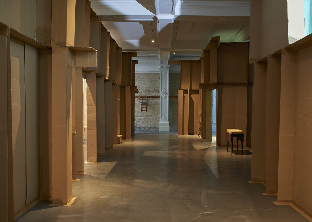The two cardboard walls reference the changing area around the gallery.