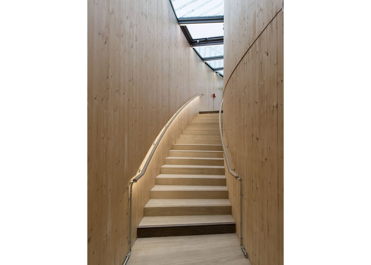 Glulam lined stairs take you up to the balconies.