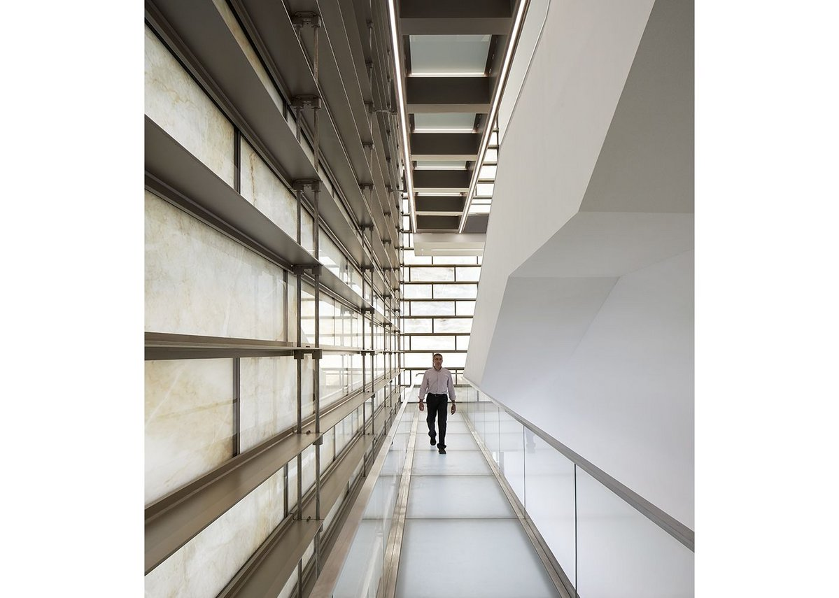 Daylight passing through the marble wall creates decorative shadows during the day in the cube's stairwell.