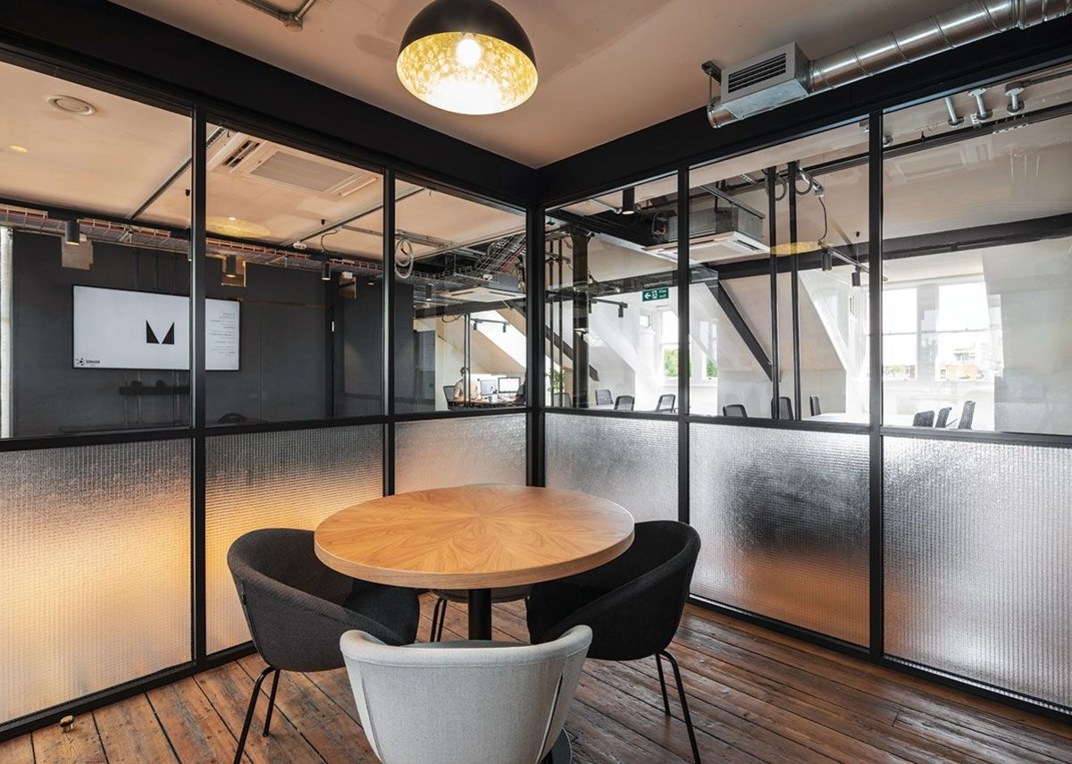 Japanese-style partitions, in glass, form offices and meeting rooms.