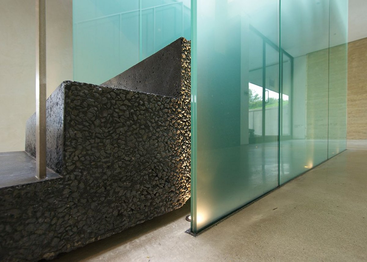 There's some bold detailing evident internally with a central staircase of black concrete and frosted green glass.