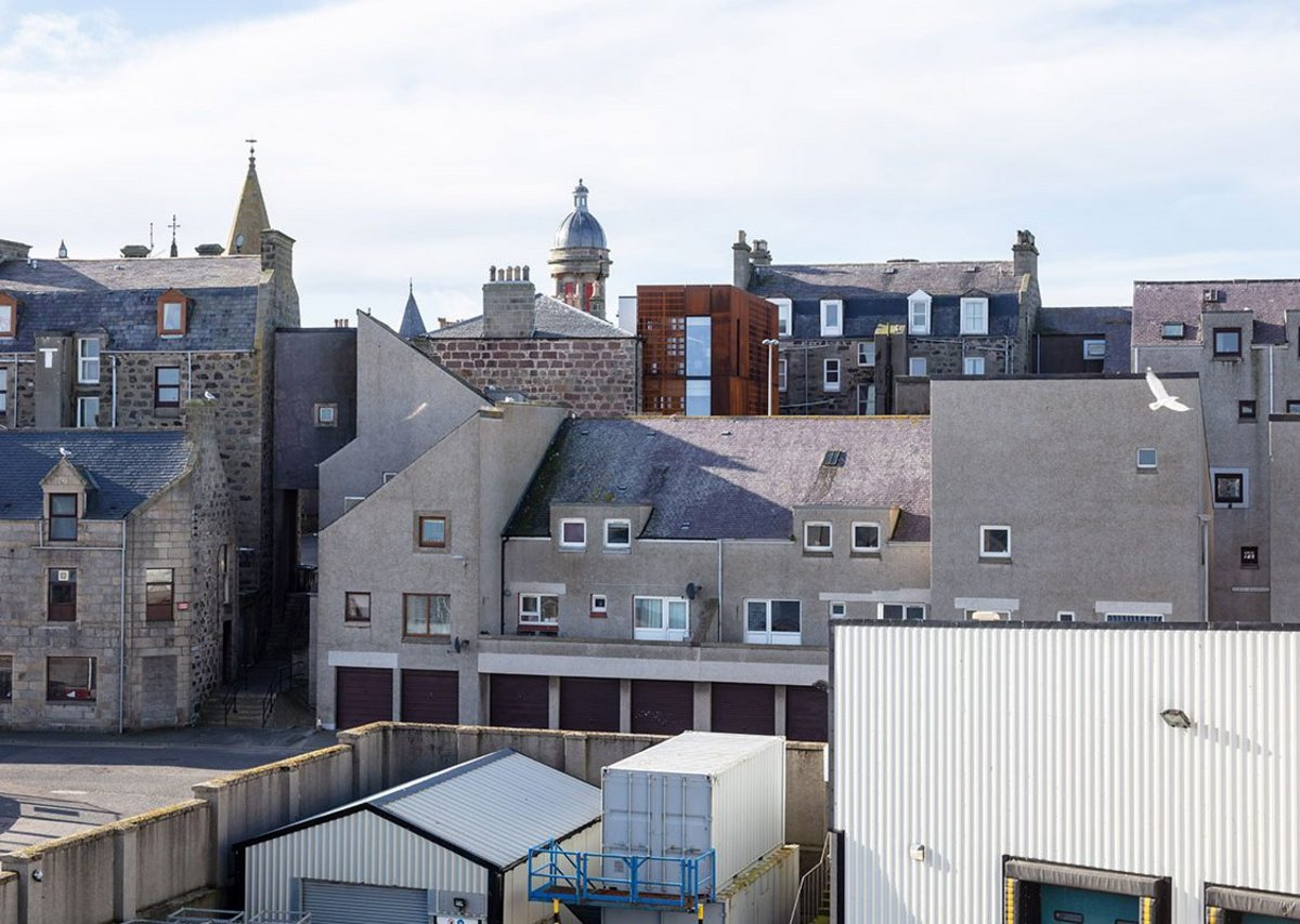 Viewed from the harbour side, the new extension slips into the existing roofscape.