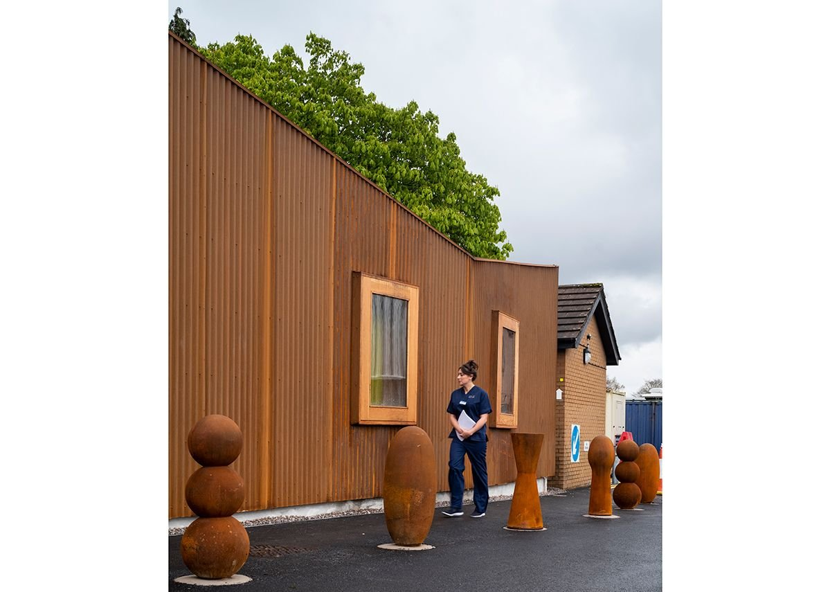 Containers and small buildings clutter the space around the back of Velindre Cancer Centre. The Maggies centre provides a more definite edge