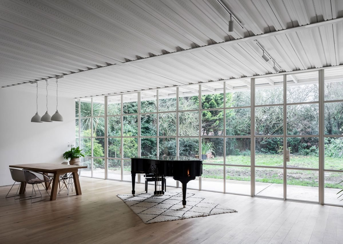 The column-free full width living/dining space exposes the steel-tray underside of the floor above: the steel-framed industrial glazing is thermally broken.