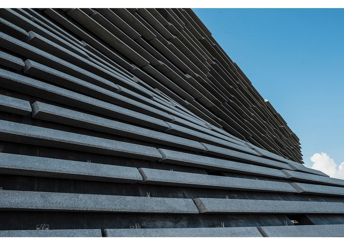 The double curve of the building's shell is dealt with by straight-line geometry of the cladding.