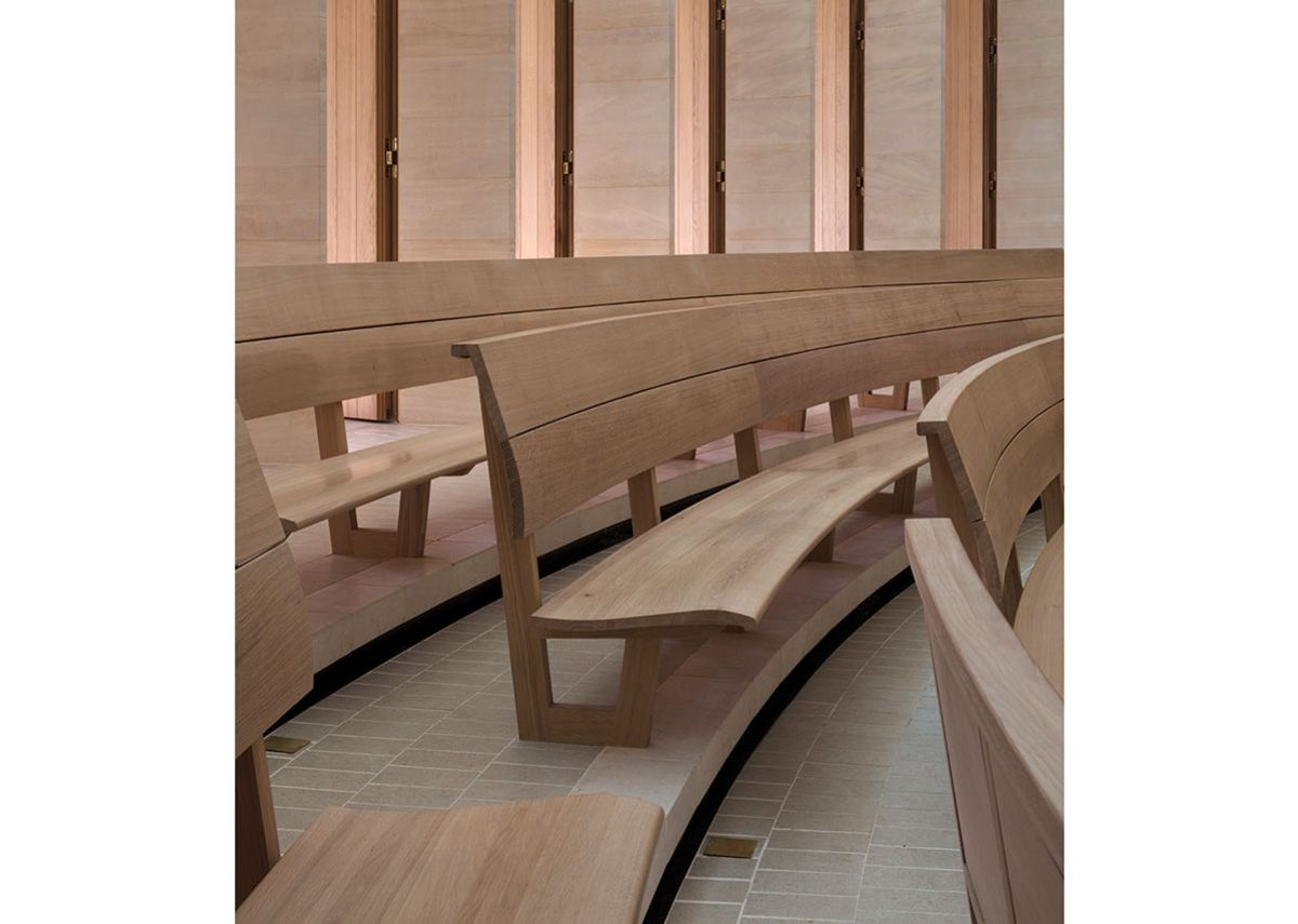 Oak benches are subtly curved for comfort. Writing flaps fold down from the back of each bench with the elegance of tiny bureaux.