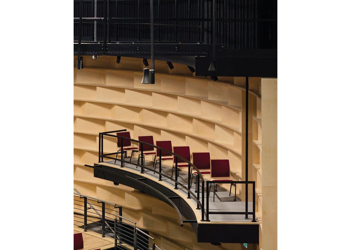 Auditorium walls are fitted with timber acoustic boxes.