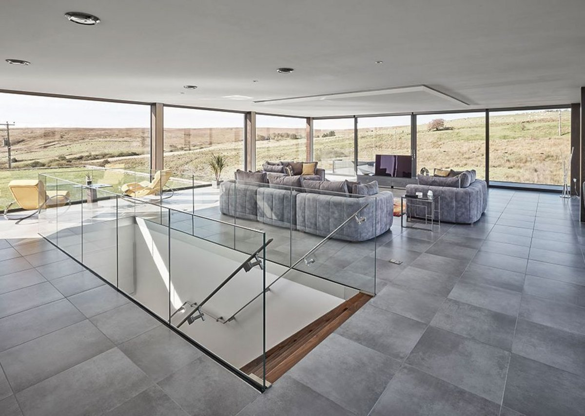 Looking from the kitchen/dining area towards the moors in the glass box, sleekly finished, the manicured grass beyond.